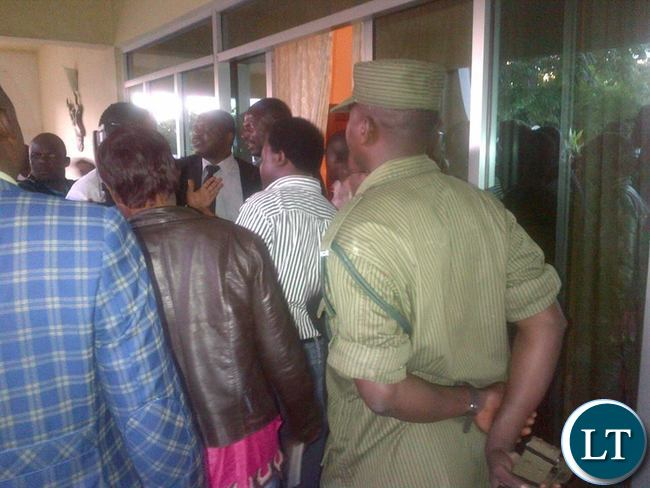 Police officers negotiating their entry into offices of Martha Mushipe's law firm