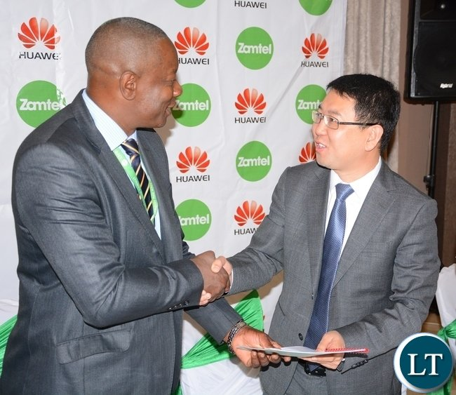 Zamtel CEO Mpanga Mwanakatwe and Managing Director Huawei Spawn Fan Wen exchange documents after Signing MOU of a Corporate Social Responsibility with Huawei Zambia provided 200, 000 USD and Zamtel Commitment to spend K2 million