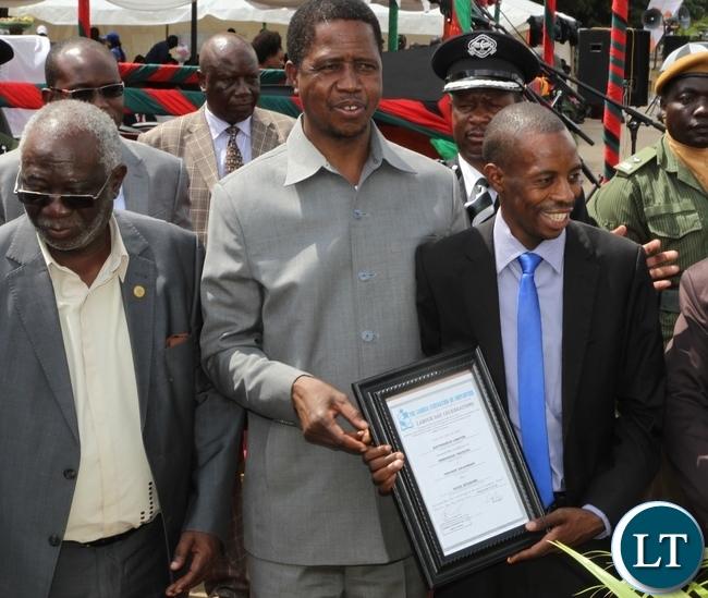 President Edgar Lungu giving Emmanuel Mazuzu of Outoworld award of Hard working whilst Labour Minister Fackson Shamenda looking on at Labour Day celebrations