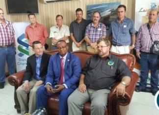 27 commercial farmers pose with Ambassador Emmanuel Mwamba