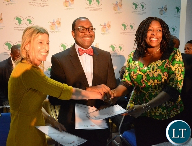 African Development Bank President Akinwumi Adesine (c) Managing Director Dangote Foundation Zouera Youssoufou (r) and Jamie Cooper Chair and President of Big Win Philanthropy exchanging documents after signing the connection with the Technical Partnership on Nutrition at the Achieving Nutritional Security conference