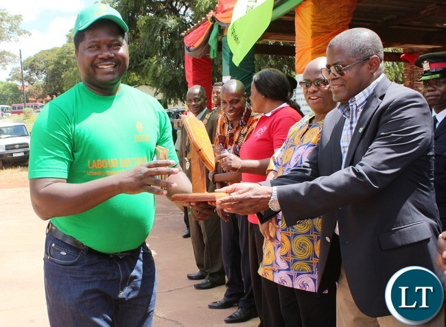 Mines and Mineral resources Minister Christopher Yaluma presents the most organized dressed ward to a ZESCO employ at President's Park in Kasama today during labour day celebrations. looking on is norther PS Hlobotha Nkunika