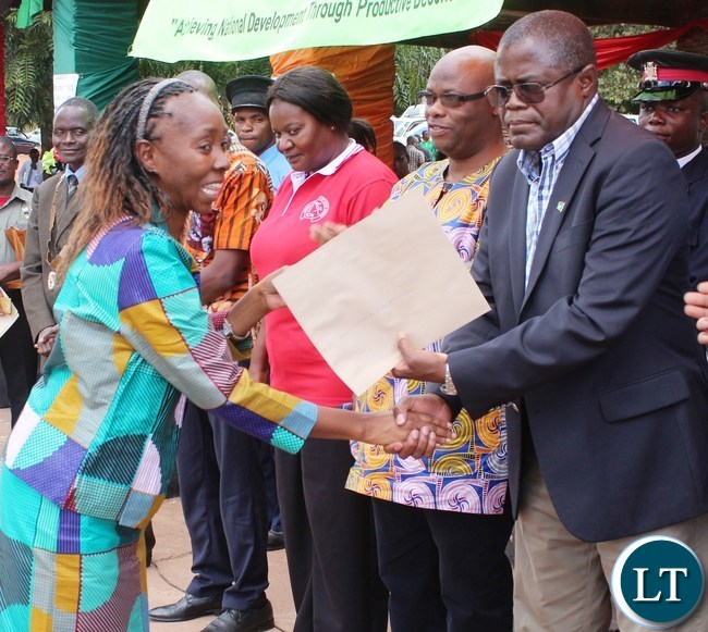 Mines and Mineral resources Minister Christopher Yaluma presents an award Principal Forestry Officer Catherine Ngubulu for hard work at President's Park in Kasama today during labour day celebrations. looking on is norther PS Hlobotha Nkunika