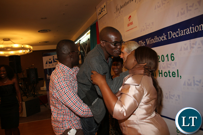 RTSA Call Centre employee Clever Zulu lifts Charles Mafa of Record and Bulletin for scooping the overal 2016 MISA award during the 2016 MISA Zambia annual awards in Lusaka on April 29, 2016.
