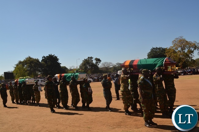 A combined team of Zambia Air Force (ZAF) and Zambia Army officers carry the caskets during the burial of Hillcrest National Technical Secondary School accident victims at Villa Grounds in Livingstone.Picture by KELVIN MUDENDA
