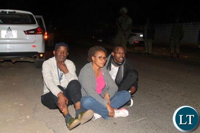 Fred Mmembe with wife Mutinta and Joseph Mwenda sit  outside Bwinjimfumu road after they were arrested
