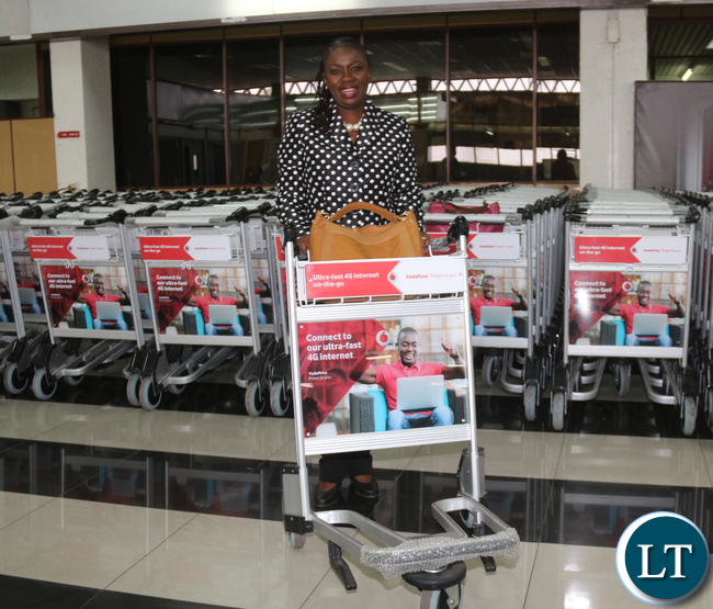Vodafone Zambia Sales & Distribution Director Mrs Leah Kooma pushing a trolley.