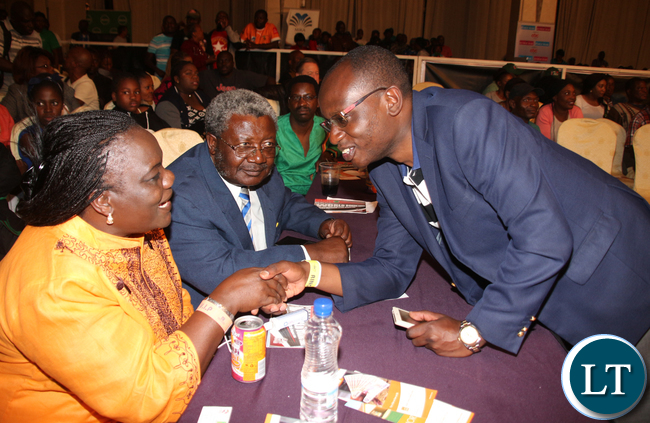 Zambia President special assistant to the press Amos Chanda conferring with Minister of Sport, Youth and Child Development PS Agnes Musunga while looking on is Sport Council chairman Mwamba Kalenga.