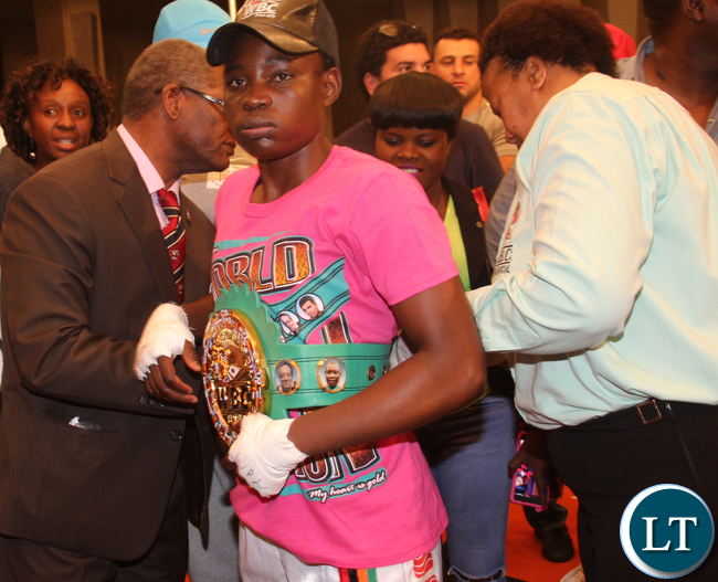 Phiri Catherine being belted by WBC board of Governors member Dr Peter Ngatane Makefetsana and WBC Referee/ Judge Silvia Mokaila.