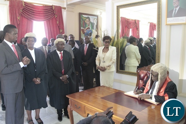 Newly appointed Speaker of the National Assembly Patrick Matibini signs in the books whilst President Edgar Lungu (l) First Speaker of the National Assembly Catherine Namugala (2nl) and second Speaker of the National Assembly Mwemba Malama (third fron left) looks on shortly after swearing in Ceremony at State House