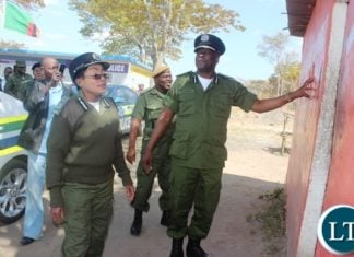 Inspector General of police Kakoma Kanganja with Central province police commissioner Lombe Kamukoshi checking on the old police office block which has since been replaced by a new one built by Herocean Enterprise Zambia at Ndabala check -point in Serenjedistrict in central province