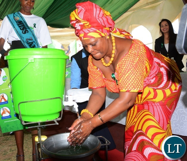 First Lady Esther Lungu washes her hands to demonstrate the 6 steps to Hand washing   during  Giacomo Global Hand Washing Day at North mead Primary School
