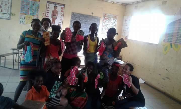 Chilufya presenting girls with reusable sanitary pads