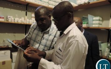 Minister of Health Chitalu Chilufya (left) with Livingstone Central Correctional Service Pharmacy Technologist Moses Kapenda (right) during the inspection of Livingstone Central Correctional Service mini Hospital in Livingstone