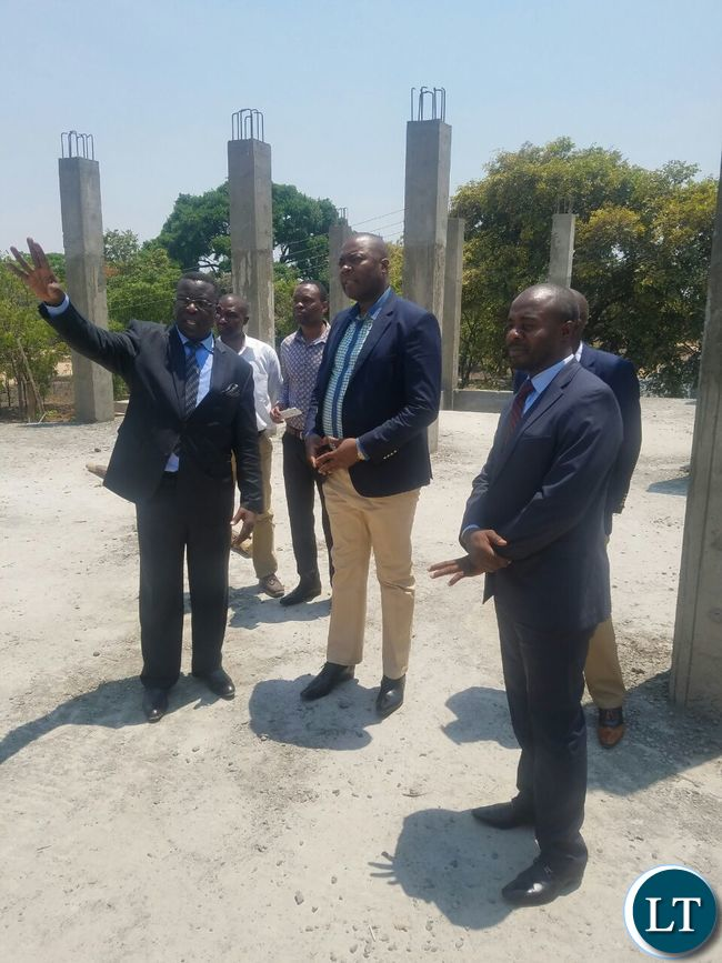 Getting a briefing from Church Reverand George Chanda on the progress on the constrcution of a new Church building