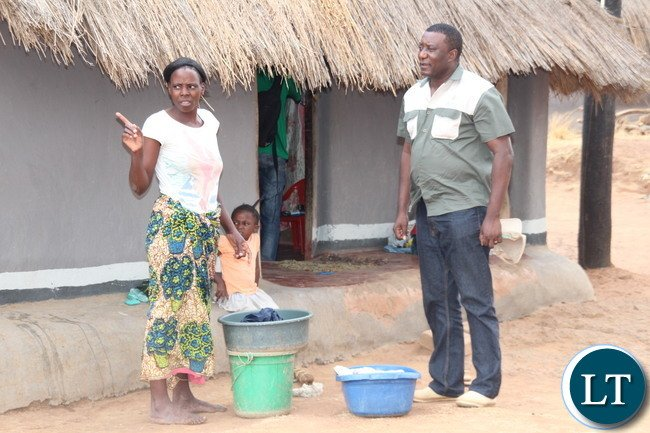 Zesco spokesperson Henry Kapata talking to Sarah Tembo, a beneficiary of newly electrified thatched house in Luangeni village in Chipata District Eastern Province. Picture by Jean Mandela