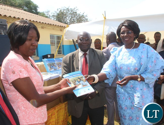 Zambia VEEP Inonge Mutukwa Wina presenting a book sample of her donation to a member of staff