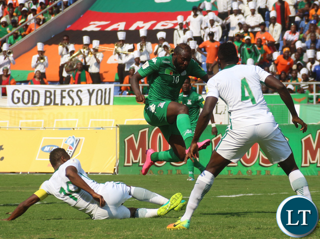 Fwayo Tembo jumps over while looking on are Nigerian players Omeruo Kenneth Josiah (4) and Mikel John Obi (10)