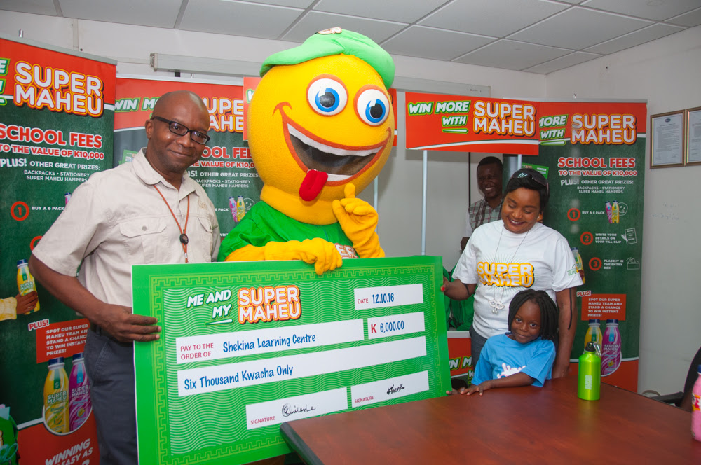 Super Maheu general manager Panji Banda presents back-to-school awards to competition winners.