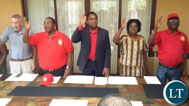 The UPND leadership singing the national anthem at the start of the media briefing