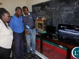 Digital Satellite Television (DSTV) Installer Sebastian Muntanga (r) instructing Kanyonyo Secondary School teachers how to operate DSTV Explorer Decoder and a TV set donated by Multi-Choice Zambia in partnership with Ministry of General Education in a program of installing free DSTV Educational Bouquets in schools in Mongu