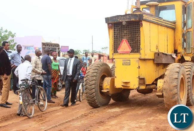 Kabwe central member of parliament Tutwa Ngulube (left in cape ) inspecting road works which he has started grading using his personal money in Kalonga ward covering a stretch of 75 kilometers in Kabwe