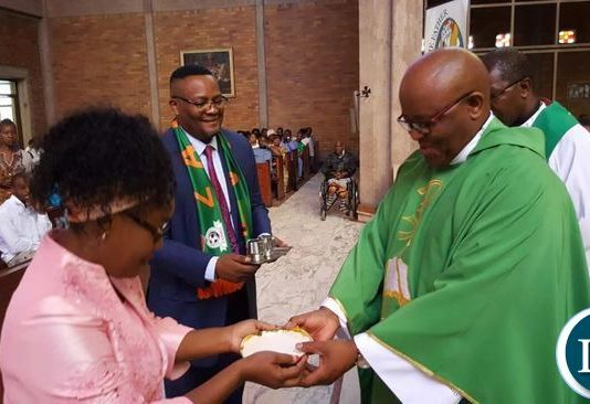 Mr. and Mrs Mwamba present the Eucharist to Father Thabo Motshegoa during the independence prayer service in Johannesburg