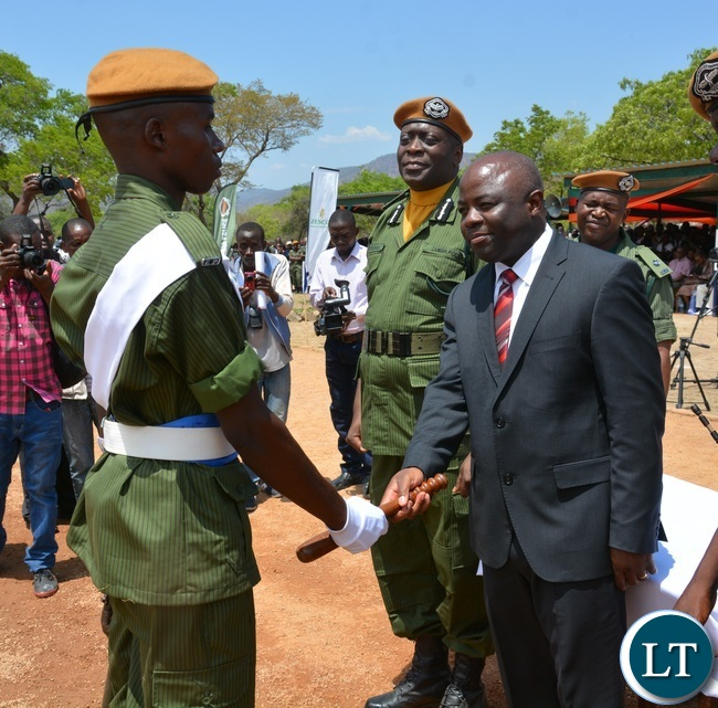 Minister of Home Affairs Stephen Kampyongo Congratulating Best overall Recruits Constables Kasongo Pole whilst Inspector General of Police Kakoma Kangaja looks on during the 2015-2016 Pass out Parade in Geoffrey Mukuma Training School or called Sondela in Kafue District