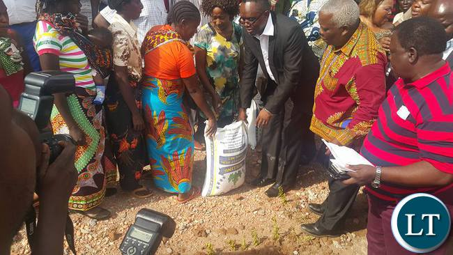 Bwana Mukuba MP Dr.Chanda hands mealie meal to victims of the storm as Minister for Presidential affairs Freedom Sikazwe looks on.