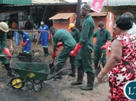 Munali Member of Parliament Prof: Nkandu Luo(r) looks on as the Zambia Army cleans up the Drainage's in Kaunda Square Stage One in Munali Constituency