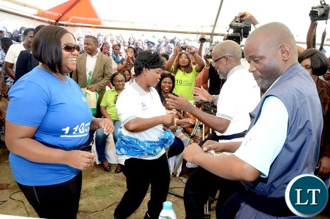 First Lady Esther Lungu and Matero member of Prliament lloyd kaziya dancing  in Lusaka's Chunga Township where she was building the house for 29 year-old widow Mary Nanyangwe on Friday,December 23,2016-PictureS by THOMAS NSAMA