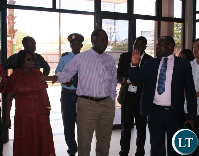 North-Western province minister Richard Kapita (m) is shown a modern civic centre constructed at a total amount of K26.3million by Solwezi town clerk Venture Kafula ( r) as Solwezi district commissioner Rosemary Kamalonga (l) looks on in Solwezi
