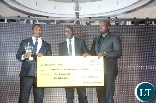 """FAZ excom Dr Joseph Mulenga, FIFA assistan Referee Kabwe Chansa and MTN Zambia Head Mobile Financial Services Wane Ng'ambi during a cheque prize presentation  of the """"2016 best assistant referee"""" to the winner."""