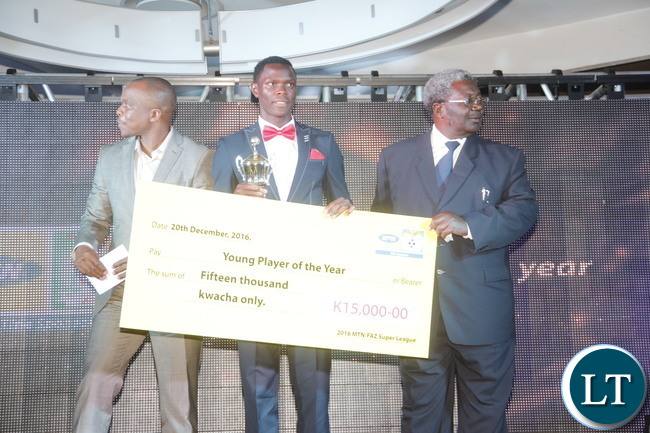 """MTN Zambia Chief Technical Officer Thomas Motlepa, Power Dynamos striker Patson Daka, National Sport Council of Zambia Chairman Mwama Kalenga during during a cheque prize presentation  of the """"2016 FAZ/ MTN league Young Player of the year""""  to the winner."""