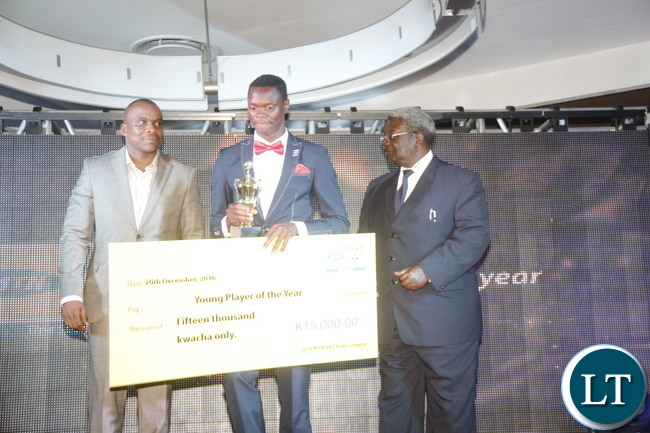 "MTN Zambia Chief Technical Officer Thomas Motlepa, Power Dynamos striker Patson Daka, National Sport Council of Zambia Chairman Mwama Kalenga during during a cheque prize presentation of the ""2016 FAZ/ MTN league Young Player of the year"" to the winner."