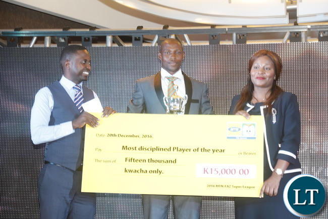 """MTN Zambia Chief Marketing Officer Felix Kamenga, ZESCO goal keeper and captain Jacob Banda, Minister of Information and Broadcasting Kampamba Mulenga during a a cheque prize presentation  of the """"2016 FAZ/MTN league Most Disciplined  player """"  to the winner."""