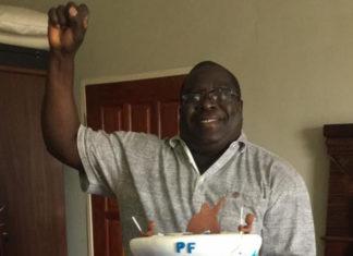 Kambwili displays his birthday cake whilst raising a fist, a PF symbol