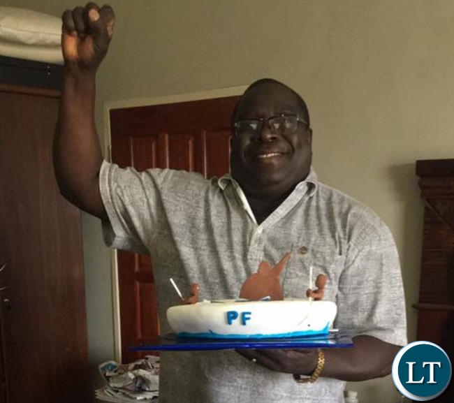 Kambwili displays his birthday cake whilst raising a fist, a PF symbol