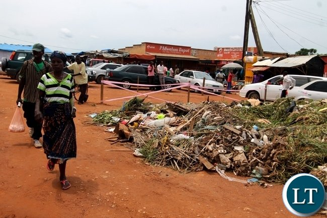 A Woman passing through uncollected garbage at UB Market in Mansa Town.