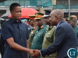 President Edgar Lungu(l) greets Lusaka Province Minister Japhen Mwakalombe(r) before departure for Chipata at City Airport
