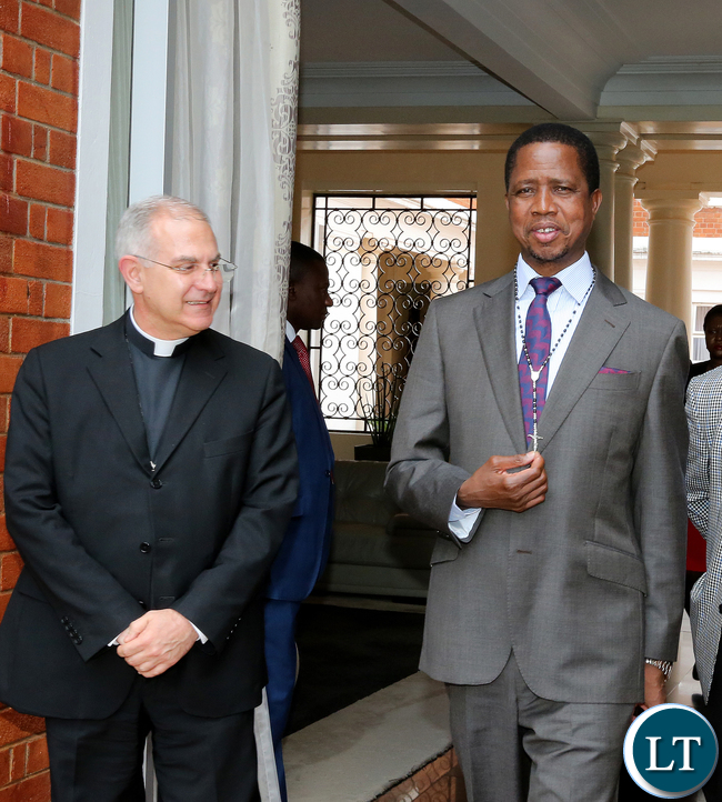 The Apostolic Nuncio to Zambia Julio Murat on February 8,2017 presented a rosary to President Edgar Lungu when he paid a courtesy call on him at State House. Here, President Lungu being helped to wear a rosary by Presidential Affairs minister Freedom Sikazwe -Picture by EDDIE MWANALEZA