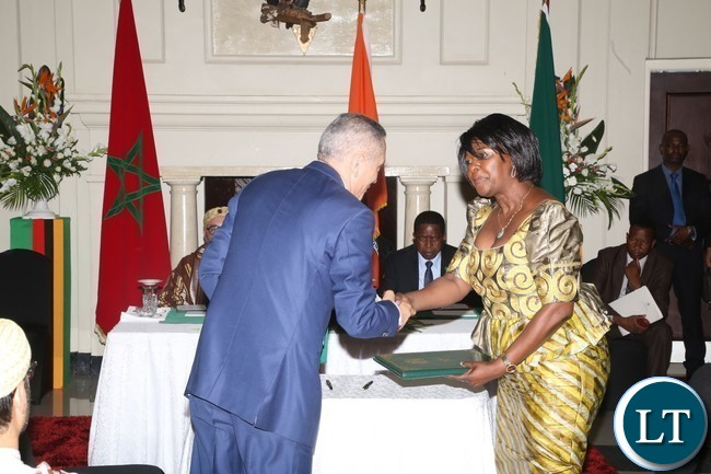 Minister of Commerce Margaret Mwanakatwe and his Moroccan  counterpart Minister of Economy and Finance Moulay Hafid Elalamy shake hands after signs agreement on MOU industrial Co-operation at State House