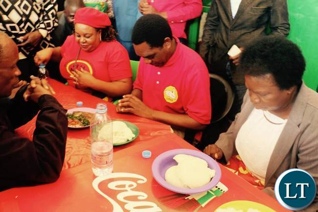 HH says a prayer before eating a plate of Nshima at Chelstone market