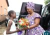 First Lady Esther Lungu receives a banquet of flowers from 12 years old girl Charity Daka during the hand over of food hampers to beneficiaries of Misissi Health Outreach Center at St.Lawrence Parish in Kamwala South.