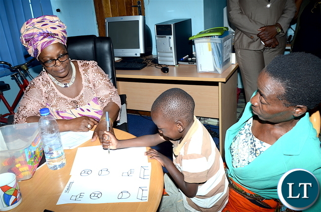 First Lady Esther Lungu interacts accesses one of the physically challenged children Benjamin Banda at Zambia Institute of Special Education where she flagged off the International Women's Day activities under the theme: Promoting inclusiveness in economic participation as a means of attending sustainable development on Friday, March 3,2017 -Pictures by THOMAS NSAMA