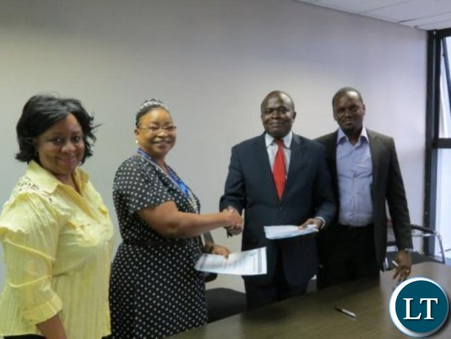 From L-M-Finance E.D Operations Ms. Zandile M. Shaba , NLS CEO Ms. Alfelt Abio-Gunda , M-Finance MD Mr. Titus Waithaka and NLS Head of Innovation Edward Kimani during a contract signing ceremony at Madison Group offic