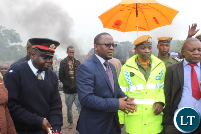-Central province permanent secretary Chanda Kabwe and central province deputy police commissioner Yobe Luhana inspecting the accident scene where 42 passengers boarded in the marcopollo escaped death after the bus Reg ADD 5736 they were traveling in ,belonging to power tools was hit by a fuel tanker truck Reg number ACV 8404 along the great north road near prospects police.
