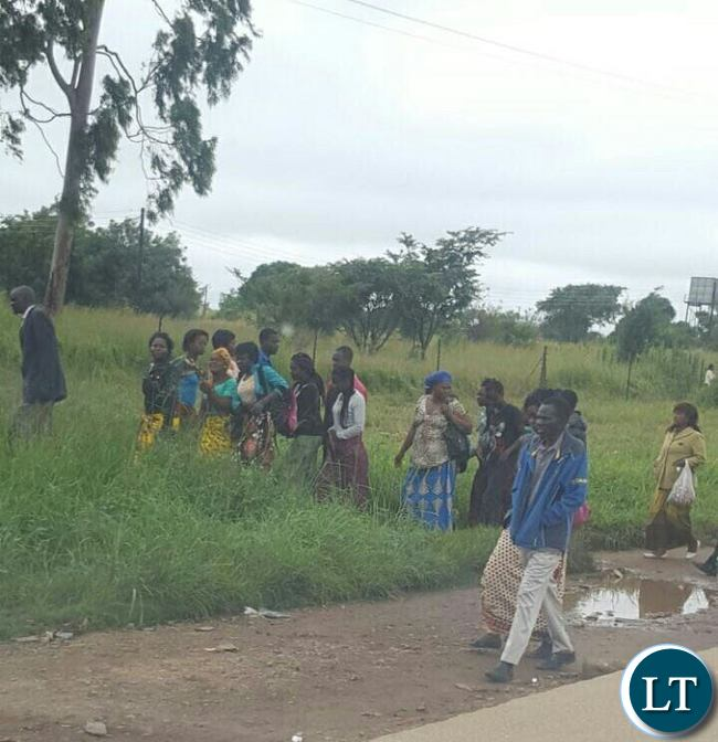 Lusaka residents braving the morning showers to line up for free food