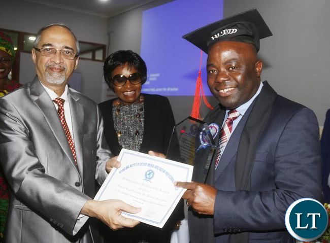 Home Affairs Minister Stephen Kampyongo receiving from International Institute of Certified Investigation Professionals USA inc (IICFIP) Global Chairperson Professor Rama Subramaniam a distinguished fellowship award while looking on is Home Affairs PS Professor Elwyn Chomba during the official launch of 2017 National Forensic Conference and Exhibition in Lusaka Mulungushi international Conference Center.