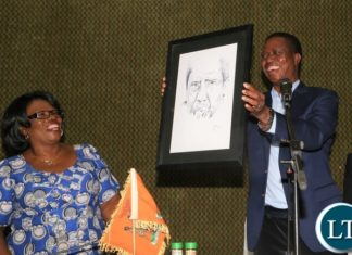 President Edgar Lungu with Higher Education Minister Nkandu Luo in a light moment whilst the President shows painted picture by Brothers Bonaventure University during the fundraising breakfast at Mulungushi Conference Centre
